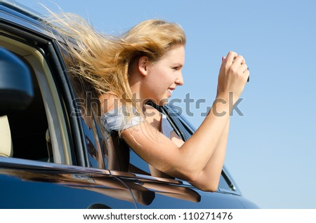 Young woman with her blonde hair blowing in the breeze leaning out of a car taking photographs