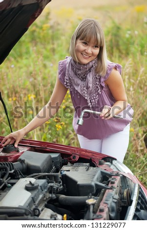 young woman with her broken car in summer day