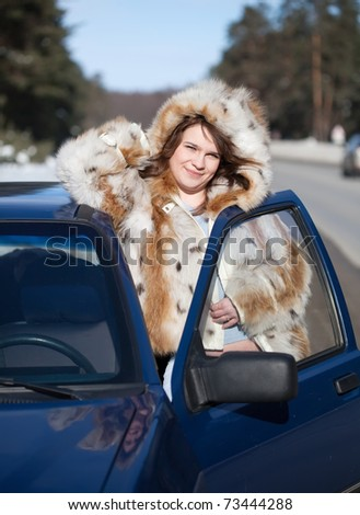 Young woman with her car in winter day