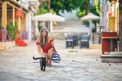 Young woman with her cat in Fiscardo, Kefalonia, Greece