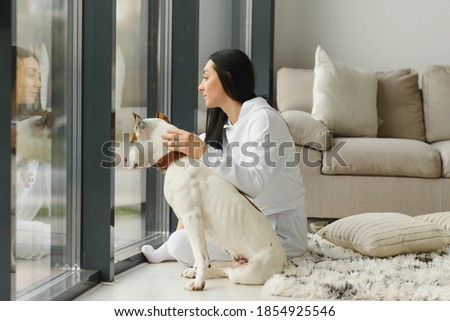 Young woman with her cute dog at home. Lovely pet