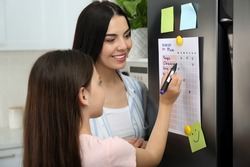 Young woman with her daughter checking to do list on fridge in kitchen