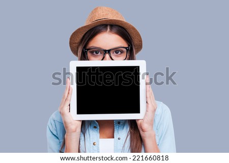 Young woman with her digital tablet. Young women holding her digital tablet in front of her face while standing against grey background