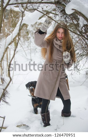 Young woman with her dog in the winter forest