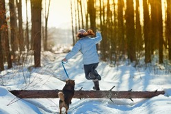 Young woman with her dog jumping over a log in snowy winter