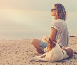 young woman with her dog on the beach watching the sunset