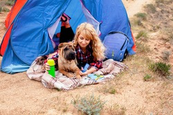 Young Woman with her dog resting in camping tent in the nature in the top of mountain with of the sea