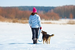Young woman with her dog walking on the snowy field