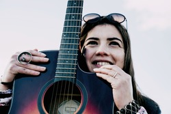 Young  woman with her guitar in the park. Concept of creative hobbiess and professionals. Female musicians. Empowerment. Selective Focus