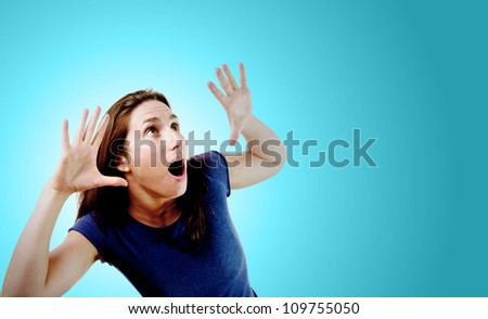 Young woman with her hands up over light blue gradient background