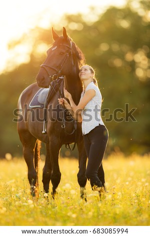 Young woman with her horse in evening sunset light. Outdoor photography with fashion model girl. Lifestyle mood