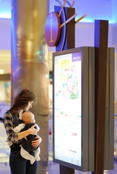 Young woman with her little baby in a shopping mall