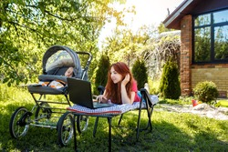 Young woman with her newborn baby lying on the grass in the park and enjoying sunny summer day. Mother with child outdoors. Motherhood.