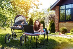 Young woman with her newborn baby lying on the soft armchair with laptop and doing selfei. Summer day. Mother with child outdoors. Motherhood.