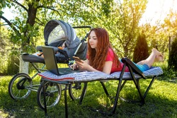 Young woman with her newborn baby lying on the soft armchair with laptop and looking at the phone. Summer day. Mother with child outdoors. Motherhood.