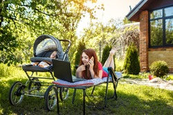 Young woman with her newborn baby lying on the soft armchair with laptop and talking on phone. Summer day. Mother with child outdoors. Motherhood.