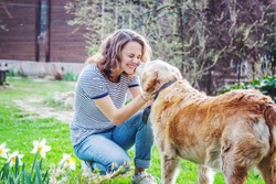 Young woman with her old dog with a golden retriever on a green lawn in front of the house