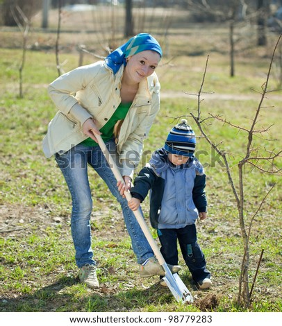 young woman with her son resetting  tree in park