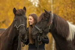 Young woman with her two best friends. Her Icelandic horses with a yellow autumn background