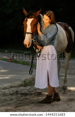 Young woman with horse in evening sunset light. Outdoor photography with fashion model girl. The girl and a horse are in the forest. Sunset. Sunrise. The model girl looks loke a cowboy. Wild West. The