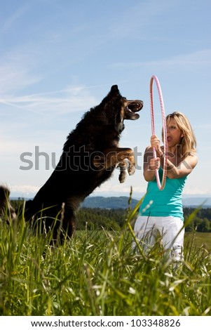 Young woman with  jumping dog on a lawn. In the background, mountains and forests