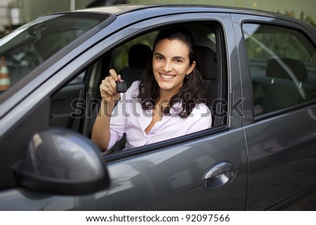Young woman with keys in a car