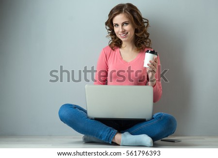 young woman with laptop and cup of coffee on gray background #561796393