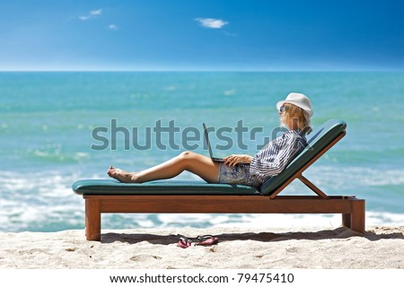 Young woman with laptop at the tropical beach