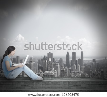 Young woman with laptop computer over urban background.