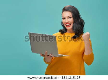 Young woman with laptop on bright light blue background. #1311315125