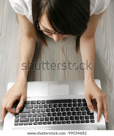 Young woman with laptop on the floor
