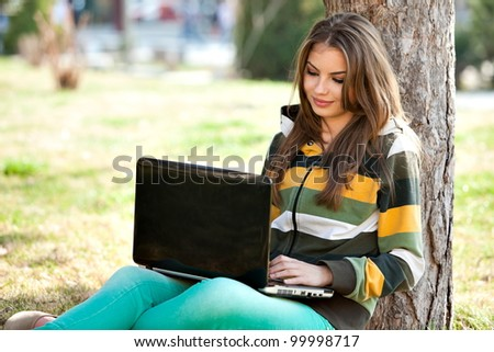 young woman with laptop, relaxing in the park