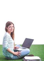 Young woman with laptop sitting on green grass . Portreit young woman