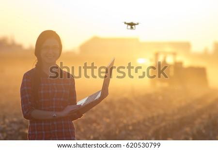 Young woman with laptop standing in field at sunset with drone above farmland