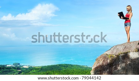 Young woman with laptop standing on cliff's edge and looking to a display