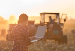 Young woman with laptop standing on field in sunset while tractor baling in background