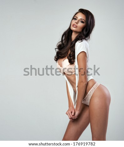 Young woman with lingerie in front of grey background