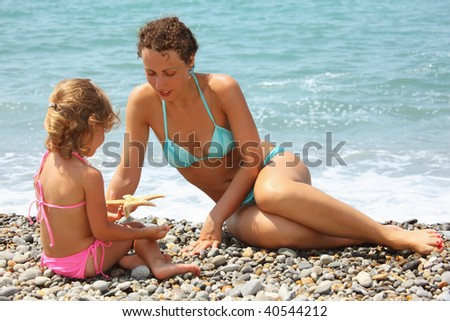 young woman with little girl played starfish on stony beach