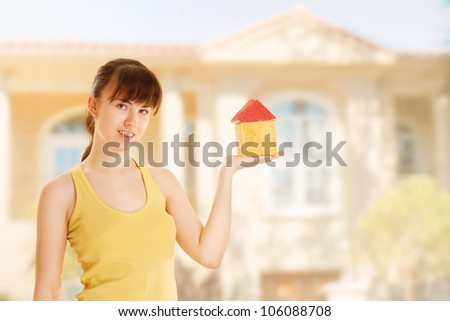 Young woman with little house
