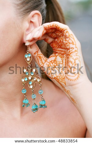 earrings and tattoo on the palm