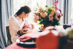 Young woman with long dark hair breastfeeding baby and sitting at large plastic panoramic window with blurry curtains on foreground at home.
