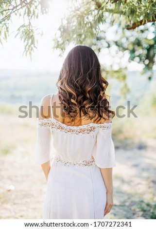 Young woman with long dark hair, wearing a bohemian white dress with open shoulders, walking in a field.  Сток-фото ©