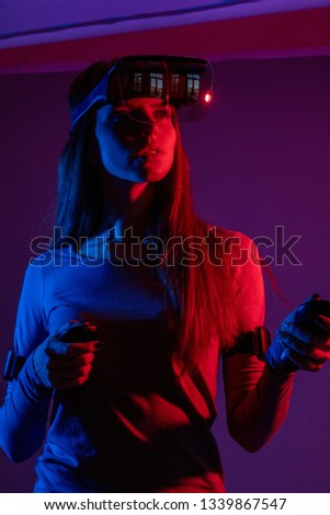 Young woman with long ginger hair sets programm for VR device to se 3 D movie, holding handheld controllers over dark background with red, blue , purple color #1339867547