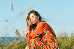 Young woman with long hair and flowery fashion orange dress posing by tall grass and blue sky. Cute modern European model girl enjoys a walk on the beach. Spring summer fashion