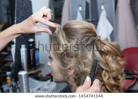 Young woman with long hair in hair salon. Barber makes a hairdress to blonde, curling curls. Concept for hairdressers and barbershop.