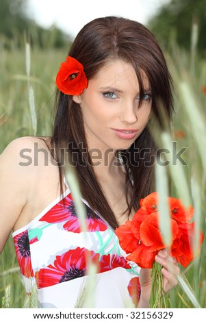 Young woman with long hair in poppies field