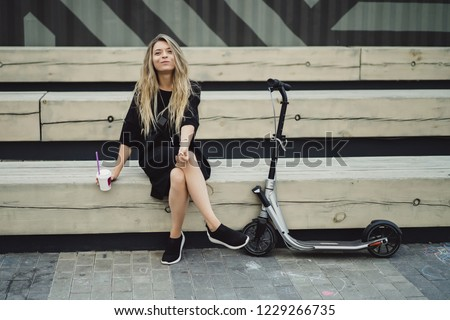 Young woman with long hairs on electric scooter. The girl on the electric scooter drinks coffee. #1229266735