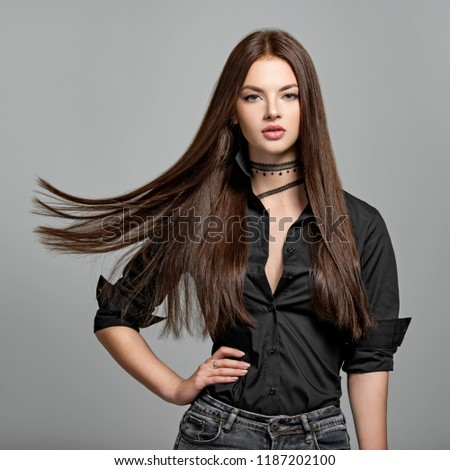 Young woman with long straight hair - at studio. Portrait of an attractive brunette girl. Fashion model wears black shirt anf jeans. Sexy female model