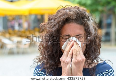 Young woman with lovely long curly hair standing outdoors blowing her nose in an urban square due to a seasonal cold or hay fever #433573729