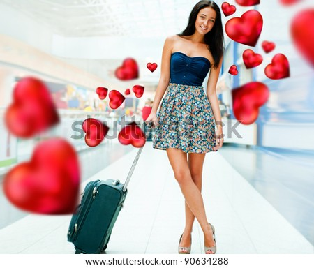 Young woman with luggage at the international airport. She is flying to her couple. Red Hearts are flying around her
